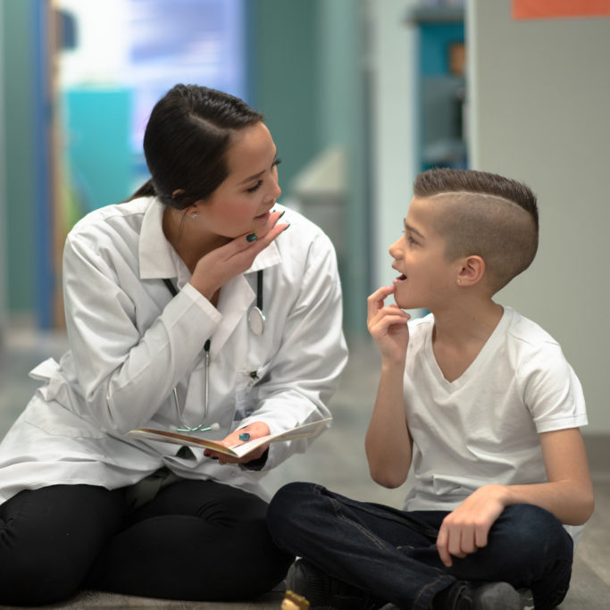 Young female speech therapist sits on floor with young male patient mouthing words to assist with verbiage and pronunciation.